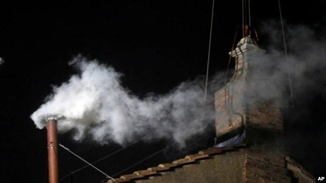 Asap putih terlihat dari cerobong asap di atap Kapel Sistina, di Lapangan Santo Petrus di Vatikan (13/3).