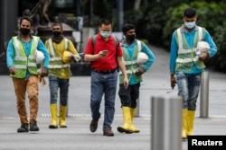 Para pekerja migran di layanan-layanan penting menyeberang sebuah jalan di kawasan Orchard Road di tengah wabah virus corona di Singapura, 27 Mei 2020. (Foto: Reuters)