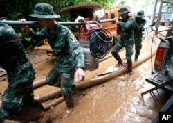 Soldiers carry a pump to help drain the rising flood water in a cave where 12 boys and their soccer coach have been missing in Mae Sai, Chiang Rai province, northern Thailand, June 29, 2018.