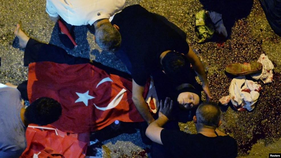 Des manifestants administrent des premiers soins à une femme blessée couverte d'un drapeau turc près de l'état-major de l'armée à Ankara, Turquie, 16 juillet 2016.