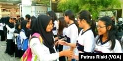 Siswa-siswi SD Kristen Petra Jombang menyalami siswa-siswi Madrasah Ibtidaiyah (MI) Islamiyyah-Plosogenuk yang mengunjungi sekolah mereka (Foto:VOA/Petrus Riski).