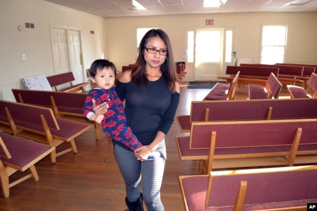 FILE - Ingrid Encalada Latorre walks with her year-old son, Anibal, where she is taking sanctuary at a Denver Quaker center, the Mountain View Friends Meeting, a small, two-story brick structure just blocks from the University of Denver, in Denver.