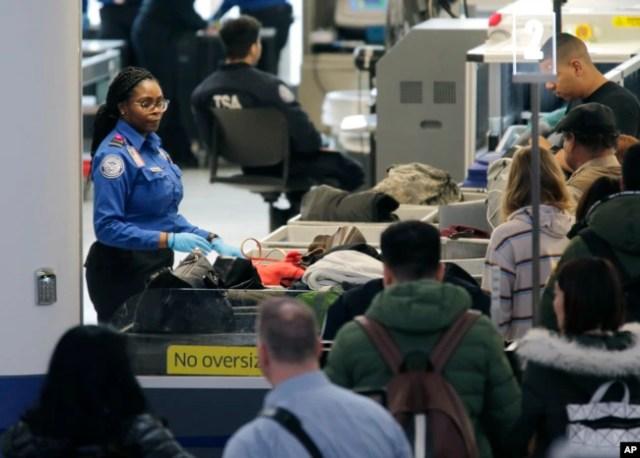 Los agentes de la Administración de Seguridad en el Transporte ayudan a los pasajeros a través de un punto de control de seguridad en el Aeropuerto Internacional Newark Liberty en Newark, N.J., el lunes 7 de enero de 2019.