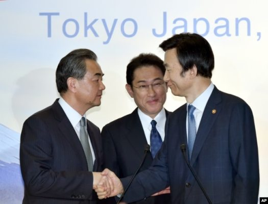 FILE - Japanese Foreign Minister Fumio Kishida, center, watches as Chinese Foreign Minister Wang Yi, left, shakes hands with South Korean Foreign Minister Yun Byung-se after the press conference following the trilateral meeting in Tokyo, Aug. 24, 2016.