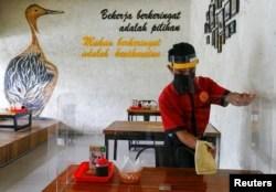 Seorang karyawan mengenakan masker dan pelindung wajah membersihkan pembatas di sebuah meja makan di restoran seiring dengan pembukaan masa PSBB transisi di Jakarta, Senin, 12 Oktober 2020. (Foto: Reuters)