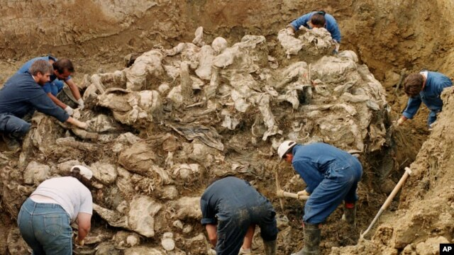 FILE - International War Crimes Tribunal investigators clear away soil and debris from dozens of Srebrenica victims buried in a mass grave near the village of Pilica, some 55 kms (32 miles) north east of Tuzla, in 2006.