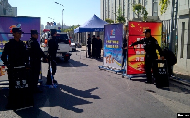 FILE - Police with riot gear guard a checkpoint on a road near a courthouse where ethnic Uighur academic Ilham Tohti's trial is taking place in Urumqi, Xinjiang Uighur Autonomous Region, Sept. 17, 2014.
