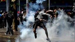 Manifestante devuelve una bomba de gas a la policía durante los choques en Santiago de Chile el lunes 21 de octubre de 2019. AP.