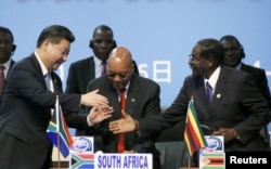 FILE - China's President Xi Jinping, left, shakes hands with Zimbabwe's President Robert Mugabe, right, while South Africa's President Jacob Zuma looks on during a Forum on China-Africa Cooperation in Sandton, Johannesburg, Dec. 4, 2015.