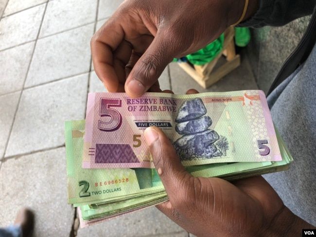 A man in Harare holds bond notes issued by Reserve Bank of Zimbabwe, Oct. 15, 2018. The introduction of bond notes - a currency Zimbabwe started printing two years ago to ease the situation -- has not helped. (C.Mavhunga/VOA)
