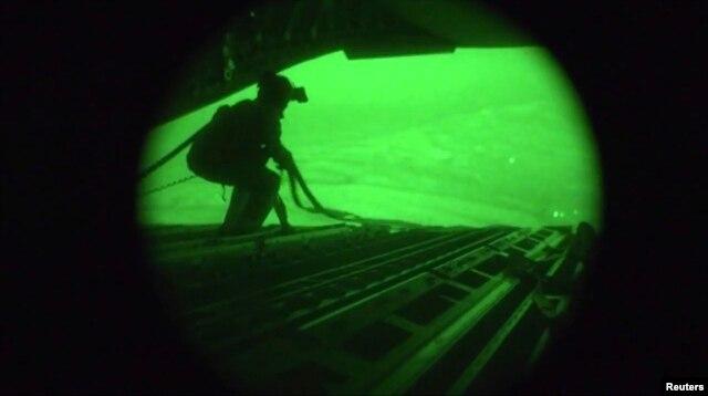 Hình ảnh video ban đêm cho thấy quân nhân Mỹ kéo dây đai lên lại trong một phi vụ quân đội Mỹ thả dù thực phẩm và nước xuống Iraq.
