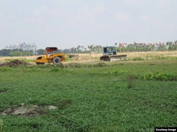 Ruộng đất của dân chưa đền bù xong nhưng các phương tiện thi công của chủ dự án vẫn ngang nhiên tiến hành san lấp. (Ảnh: Lê Anh Hùng)