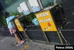 Seorang anak memakai masker dan faceshield sedang mencuci tangan di wastafel, di pusat penjualan elektronik di Surabaya (foto Petrus Riski-VOA).