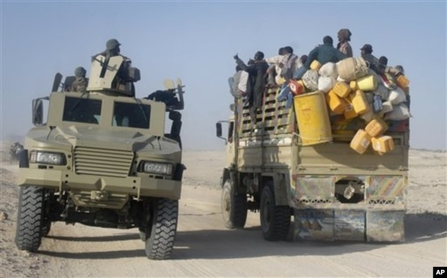 FILE - East African civilians depart in a truck, right, as AMISOM forces advance on al-Shabab-controlled region, Somalia, Sept. 4, 2012.