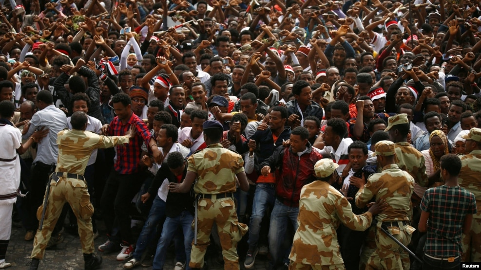 FILE - Demonstrators chant slogans and flash the Oromo protest gesture during Irreecha, the thanksgiving festival of the Oromo people, in Bishoftu town, Oromia region, Ethiopia.