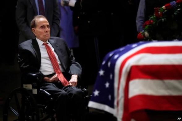 El exsenador Bob Dole, de 95 años de edad, recibió ayuda para levantarse de su silla de ruedas y saludó el féretro del fallecido expresidente George H. W. Bush.
