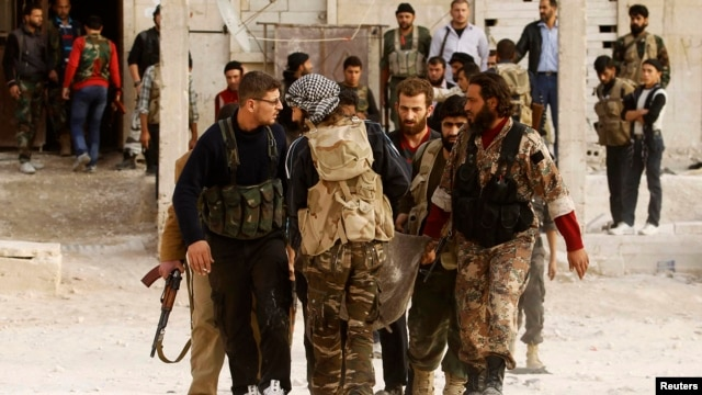 FILE - Free Syrian Army fighters carry the body of a fellow fighter who was killed during what FSA rebels say were clashes with forces loyal to President Bashar al-Assad near Aleppo International airport.