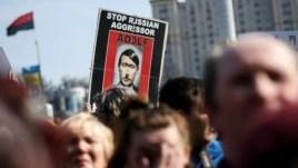 Người biểu tình cầm hình ảnh mô tả ông Putin như Adolf Hilter trong một cuộc biểu tình chống chiến tranh tại Kiev.