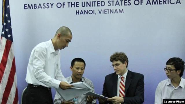 Bốn blogger Việt Nam, trong đó có anh Lã Việt Dũng, trao cho các nhà ngoại giao Mỹ tại Hà Nội 'Tuyên bố 258'.