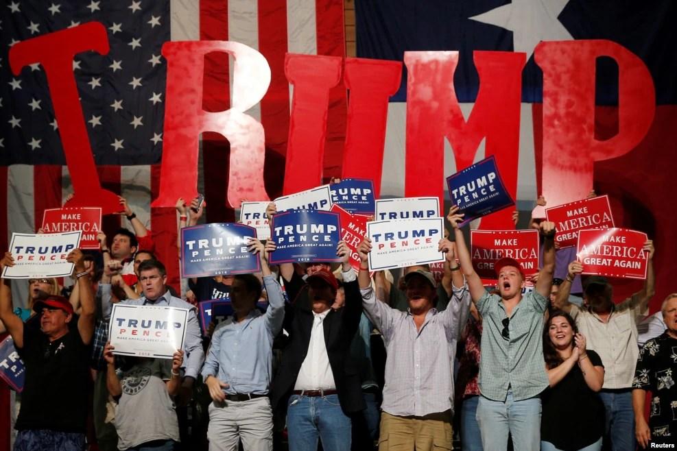"""在德克萨斯州的奥斯丁,群众在川普演讲时举着标语""""川普""""""""川普,彭斯""""和川普的竞选口号""""让美国再度伟大"""""""