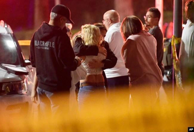 La gente se consuela entre sí frente al lugar del mortal tiroteo en Thousand Oaks, California, el jueves, 8 de noviembre de 2018.