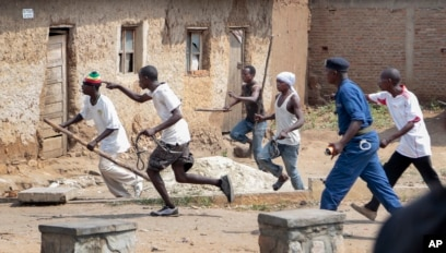 FILE - Members of the Imbonerakure pro-government youth militia chase after opposition protesters, unhindered by police, in the Kinama district of the capital Bujumbura, Burundi, May 25, 2015.