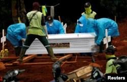 Para petugas menggunakan baju pelindung memakamkan korban virus corona (COVID-19) di sebuah pemakaman yang disediakan pemerintah, di Jakarta, 3 April 2020. (Foto: Reuters)