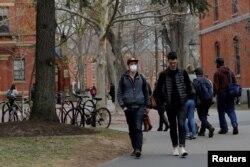 Seorang mahasiswa yang mengenakan masker, karena pengobatan kankernya telah membuatnya tertekan kekebalan dan rentan terhadap penyakit seperti virus corona, berjalan melalui Halaman di Universitas Harvard. (Foto: Reuters)