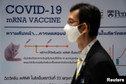 A man wearing a face mask stands next to a board showing the progress of developing an mRNA type vaccine candidate for COVID-19 during a news conference at the National Primate Research Center of Chulalongkorn University, June 22, 2020.
