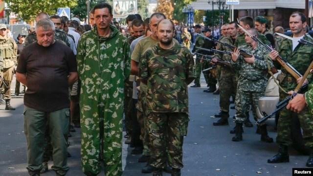 FILE - Armed pro-Russian separatists escort a column of Ukrainian prisoners of war in central Donetsk, Ukraine in 2014.