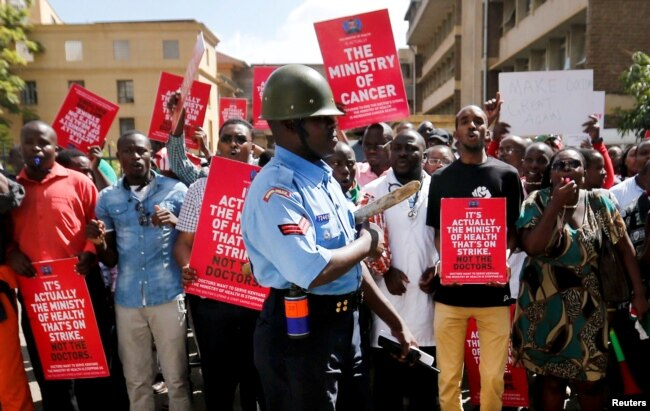 FILE - A riot policeman stands guard as doctors chant slogans after their case to demand fulfilment of a 2013 agreement between their union and the government that would raise their pay and improve working conditions in Kenya, Feb. 13, 2017.