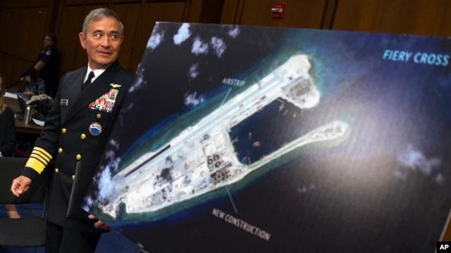 Đô đốc Harry Harris đi ngang qua bức ảnh cho thấy một hòn đảo mà Trung Quốc đang xây dựng trên đảo Đá Chữ Thập ở Biển Đông.