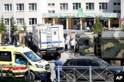 Sebuah ambulans dan truk polisi diparkir di sebuah sekolah usai penembakan di Kazan, Rusia, Selasa 11 Mei 2021. Media Rusia melaporkan bahwa beberapa orang tewas dan terluka dalam penembakan di sekolah di kota Kazan, Rusia.