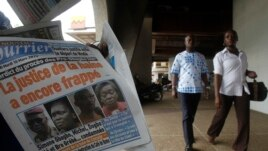 People walk past a man selling a copy of Le Nouveau Courrier, which has a picture of Ivory Coast's former first lady Simone Gbagbo (2nd L, on newspaper), in Abidjan, March 10, 2015.