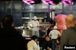 Seorang penjual menyiapkan pizza di sebuah food truck di Al Aali Mall di Manama, Bahrain, di tengah pandemi COVID-19, 27 Februari 2021. (REUTERS)