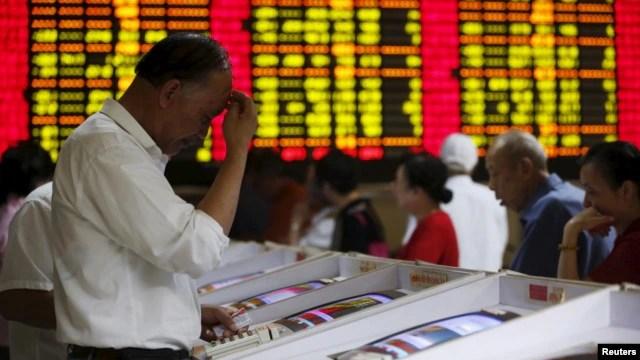 Nhà đầu tư nhìn vào màn hình máy tính hiển thị thông tin chứng khoán tại một trung tâm môi giới ở Thượng Hải, Trung Quốc.
