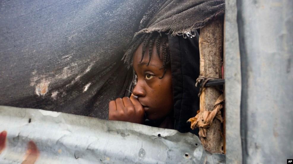 Một bé gái đang đợi để được sơ tán ra khỏi nhà tại Tabarre, Haiti.