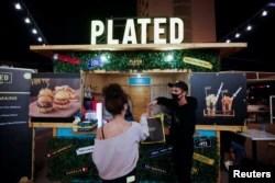 Seorang pelanggan mengambil pesanannya dari food truck hamburger di Al Aali Mall, di Manama, Bahrain, di tengah pandemi COVID-19, 27 Februari 2021. (REUTERS/Hamad I Mohammed)