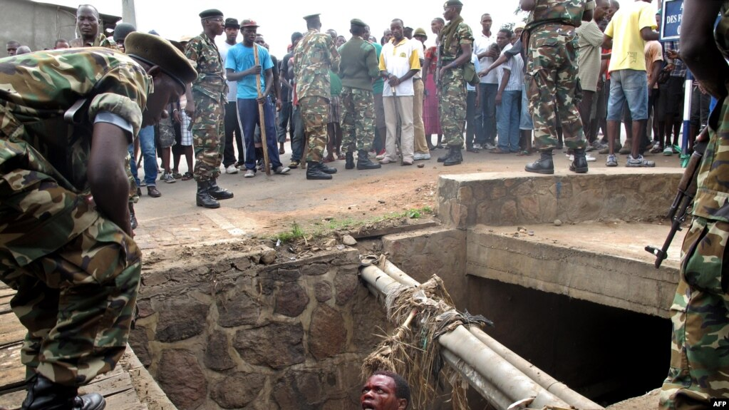 FILE - A man begs for help from the military as he stands in a drain where he had hidden to escape a lynch mob at the Cibitoke district of Burundi's capital, Bujumbura. International judges have approved the opening of a full investigation into alleged crimes against humanity in Burundi, where at least 1,200 people have died in unrest since 2015.