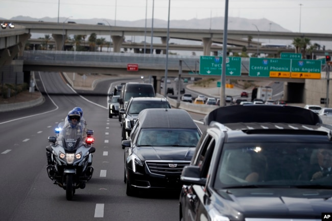 Una caravana que lleva el atáud del senador John McCain se desplaza desde el Capitolio estatal en Phoenix, Arizona, hasta la North Phoenix Baptist Church para un servicio recordatorio el jueves, 30 de agosto de 2018.