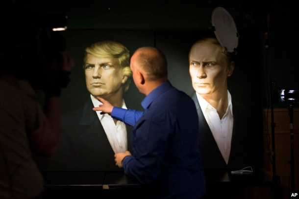 2016年11月9日,一名俄罗斯记者用手指指着川普的画像。右边是普京总统的画像。