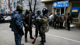 Armed men stand in front of police headquarters in Slaviansk, April 12, 2014.