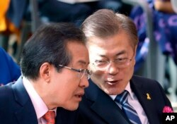 South Korean presidential candidates Hong Joon-pyo, left, of the Liberty Korea Party and Moon Jae-in of the Democratic Party confer as they attend a service to celebrate Buddha's birthday at the Jogye temple in Seoul, South Korea, May 3, 2017.