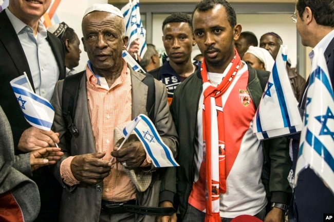 Ethiopian Jews hold Israeli flags at the Ben Gurion airport near Tel Aviv, Israel, Feb. 4, 2019.