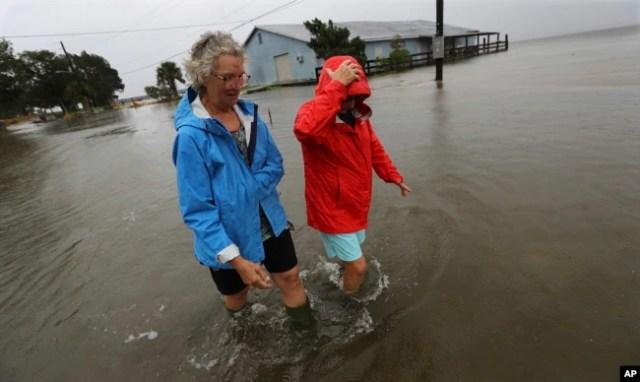 Dos residentes de St. Mary, en Georgia, caminan cerca de sus casas el 4 de septiembre de 2019, luego del paso del huracán Dorian. Curtis Compton/Atlanta Journal-Constitution via AP.