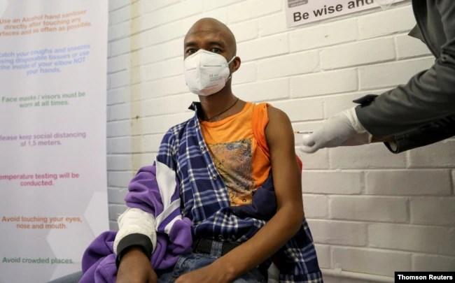 Seorang sukarelawan menerima suntikan dari seorang pekerja medis selama uji klinis manusia pertama di negara itu untuk vaksin potensial melawan virus corona baru, di Soweto. (Foto: Reuters)