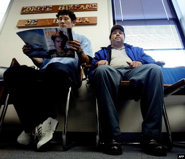 Un ciudadano salvadoreño, a la izquierda, acompañado por un amigo (derecha), espera en el vestíbulo del Comité Hispano de Virginia, en Falls Church, Virginia, el 11 de noviembre de 2002, para obtener ayuda con su documentación de inmigración de EE.UU. para extender su Estado de Protección Temporal (TPS).
