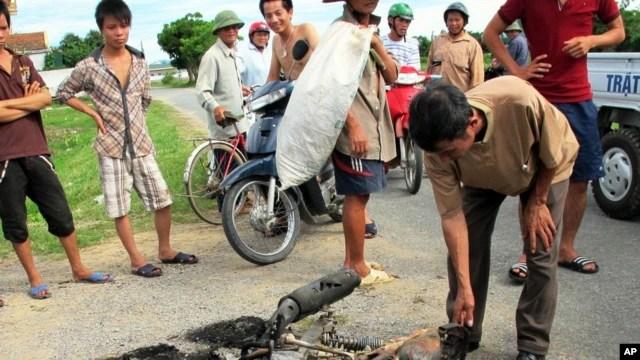 Cư dân vây quanh một chiếc xe máy bị cháy thành than trong tỉnh Nghệ An. Dân làng phẫn nộ vì bị trộm chó đã thu giữ xe máy của các tên trộm chó và nổi lửa đốt xe.