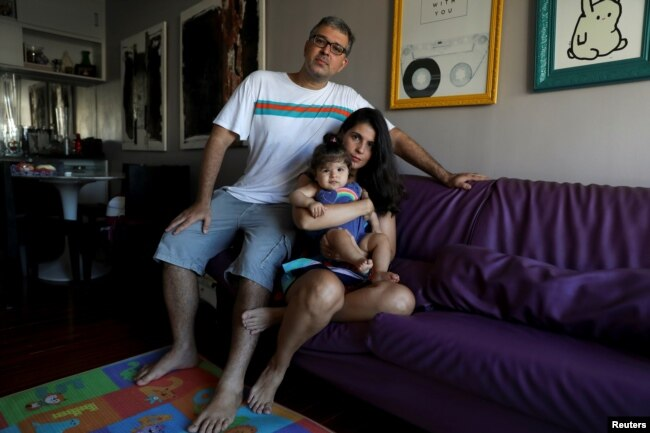 Tatiana Barcellos, 37, a civil servant for the Federal Prosecutor's Office, her eight-month-old daughter Alice, and her husband Marcelo Valenca, 39, a teacher at a navy school, pose for a photograph on the day Tatiana went back to work, at their home in Rio de Janeiro, Brazil, Jan. 28, 2019.