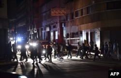 FILE - People cross a street during a power cut in Caracas, March 7, 2019.